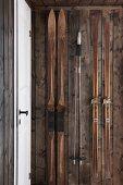 Retro skis hanging on dark board wall