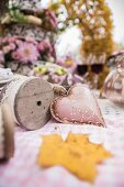 Metal heart and reel of decorative ribbon on autumnal table