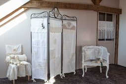 Metal screen covered in white lacy fabric next to chairs with vintage-style accessories