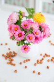 Daisies and dahlias in white jug surrounded by scattered hazelnuts