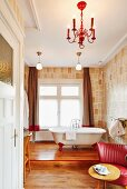 Free-standing bathtub on wooden platform behind table and red retro armchair in bathroom with designer wallpaper