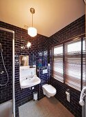 Bathroom with dark blue tiles, white fittings and closed louvre blinds on window