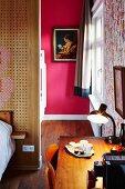 Desk in bedroom and view of artwork on hot pink wall seen through open doorway