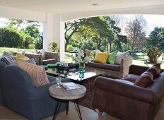 Various sofas and wicker furniture on roofed terrace with view of large garden