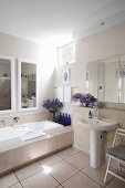 Bathtub with wide tiled surround, large mirror, blue bottles and bouquets