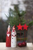 Christmas figurines, red apples and star decorations in front of fir branches in metal bucket