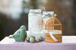 Romantic arrangement of quails' eggs, bird ornament, miniature bird cage and decorated screw-top jars
