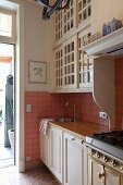Kitchen counter with white base units and country-style wall units with lattice doors