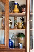 Collection of jugs, bottled and figurines in dresser with open glass door