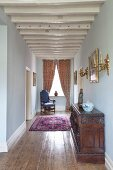 White-painted, restored wood-beamed ceiling in narrow hallway of period apartment furnished with period furniture