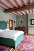 Double bed with turquoise upholstery and white bed linen in traditional bedroom with pink-painted wood-beamed ceiling and pastel turquoise walls
