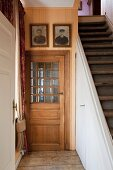 Traditional interior fittings: panelled wooden door with glass insert next to staircase with storage space below