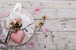 Pink heart-shaped ornament and posy of dried roses on vintage-style plate on rustic wooden surface scattered with flowers