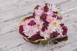 Heart-shaped arrangement of chrysanthemums and autumn leaves