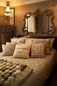Collection of scatter cushions on French bed below Baroque mirror in ornate gilt frame in vintage-style bedroom