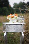 Festliches Blumengesteck mit Silberschmuck und Kerzenlaternen mit Vogelfigur auf versilbertem Tisch
