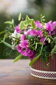 Gesteck aus violetten und weissen Erbsenblüten, Mohnkapseln und Efeu im Übertopf mit gemusterter Bordüre