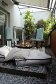 Floor cushions and vintage chairs with pale blue upholstery around fire bowl on balcony with pebble floor