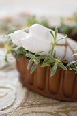 White candles in planted container on embroidered vintage tablecloth