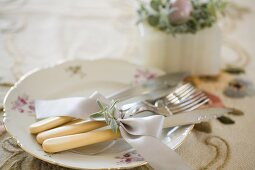 Vintage cutlery with cream plastic handles tied with ribbon on gold-rimmed plate
