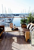 Outdoor furniture on sunny wooden terrace with yachting marina in background