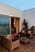 Twilight atmosphere on Mediterranean terrace with wicker furniture