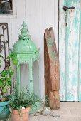 Arrangement mit nostalgischem Laternen-Windlicht und bedrucktem Holzbalkenstück vor verwitterter, türkisfarbener Vintagetür