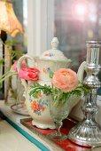 Lachsfarbene Ranunkelblüte, Kerzenständer und nostalgischer Kaffeekanne auf Fenstersims