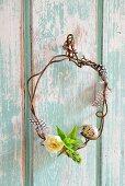 Kleiner Kranz aus rostiger Draht mit Wachtelei, Federn und Narzissenblüte an Holzwand
