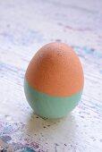 Osterei, bis zur Hälfte mintgrün lackiert