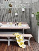 Vintage table and benches and planters hanging from grey-painted wooden screen