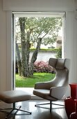 Designer easy chair with footstool by Antonio Citterio in front of window with garden view