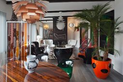 Round table below classic pendant lamp in front of lounge area with retro armchairs and palm in orange pot