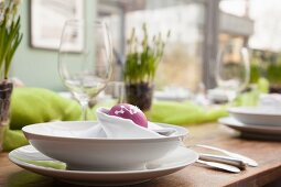 Place setting with purple Easter egg in napkin nest