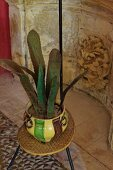 Plant-shaped ceramic artworks in pot on vintage plant stand