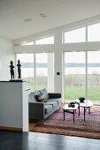 Geschwungenes, mehrteiliges Couchtisch-Set und grauer Dreisitzer auf Teppich vor raumhoher Glasfront