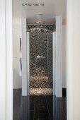 Blick in bodenebenem, abgetrenntem Duschbereich mit Mosaikfliesen, im Designerbad