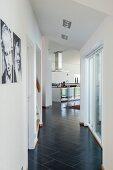 Gangbereich mit schwarzem Fliesenboden in Diagonalverlegung, im Hintergrund offen Küche