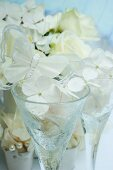 Stemmed glasses decorated with white hydrangea florets and butterfly ornaments in front of hydrangea plant