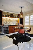 Retro chairs at round table with glass top on animal-skin rug in home bar with illuminated stone wall