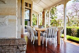 White wicker chairs at wooden table on reddish wooden floor of veranda with white wooden pillars
