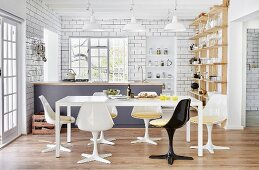 Retro shell chairs around white table in open-plan kitchen with counter and white-tiled walls