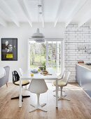 Retro shell chairs around white table in open-plan interior with terrace doors