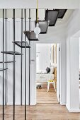 Steel staircase in hallway and view of retro stool next to bed seen through open door