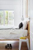 Retro stool next to wood-framed bed seen through open door