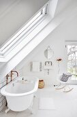 Free-standing vintage bathtub and classic rocking chair below sloping ceiling in white bathroom