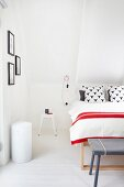 Bed with red-and-white-striped bedspread and retro stool used as bedside table in attic bedroom