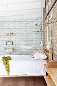 Double bed with wooden frame below pendant lamps and against brick wall in front of glass partition screening shower area with white-tiled wall