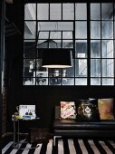 Side table next to black leather couch and arc lamp in front of Industrial interior window in masculine loft apartment
