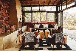 Blankets on backrests of leather chairs and solid wooden side tables in Colonial-style living room